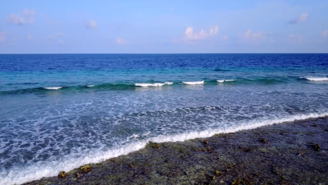 v04255 Aerial flying drone view of Maldives white sandy beach on sunny tropical paradise island with aqua blue sky sea water ocean 4k video
