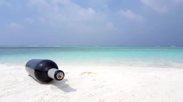 v07566 Maldives white sandy beach bottle on sunny tropical paradise island with aqua blue sky sea water ocean 4k video