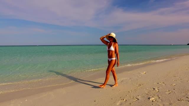 v07947 Maldives white sandy beach 1 person young beautiful lady sunbathing alone on sandbar on sunny tropical paradise island with aqua blue sky sea water ocean 4k video