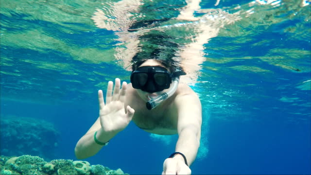 Vacation at sea. A masked man with a tube floats near the surface of the water, waving his hand at the camera video