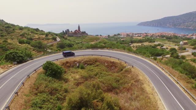 AERIAL Van driving on road leading to village of Komiza video