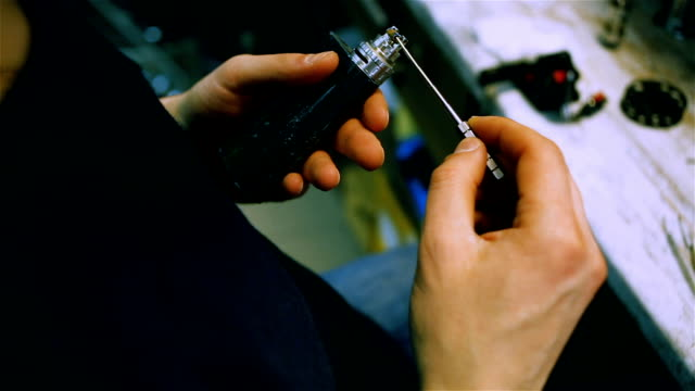 Vape. Male hands regulate electronic cigarette coils. After-sales service of the e-cigarette. video