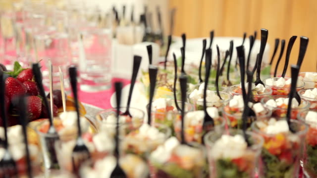 Various appetizers, desserts, drinks, vegetable salad at a banquet on catering video
