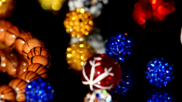 Various colors of beads isolated on black background, close up video