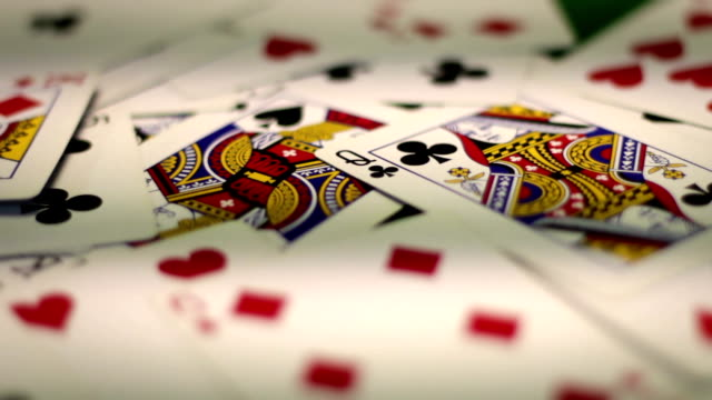 Various designs of poker playing cards on old poker table video
