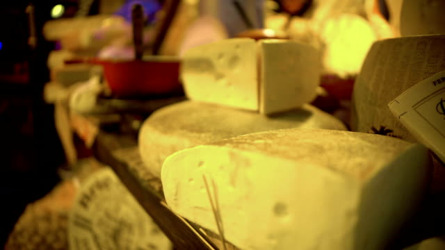 Various expensive cheeses lying on showcase at gourmet shop, food production video