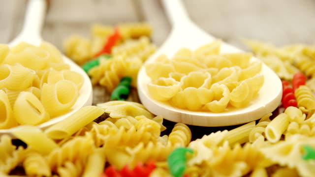 Various pasta in spoons on wooden background video