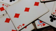 Various playing cards rotate on table. video