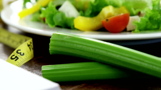 Vegetable salad in plate with measurement tape and spiral notebook on table video