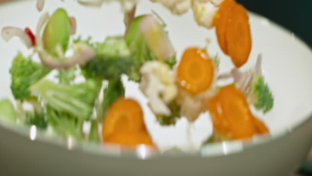 SLO MO Vegetables being tossed in a white pan video