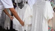 Vegetarian female choosing a white clothes for vegetarian festival in Thailand. video