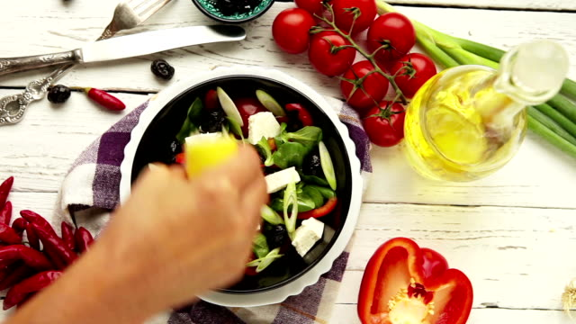 Vegetarian low calorie Greek salad preparation top view lemon juice addition moment video