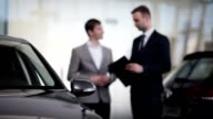 Vehicle dealer assisting client in a motor show video