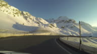 Vehicle POV driving on snowy mountain road at sunset video