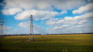 Vehicle long shot of wind farm park and power grid lines and poles green grass video