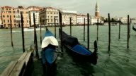 Venetian gondolas rock on the gentle waves of one of the canals on the background of beautiful architecture video