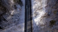 AERIAL, vertical: Cars driving along the road in winter, slow motion video