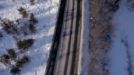 AERIAL, vertical: Driving cars on a rural road in winter video