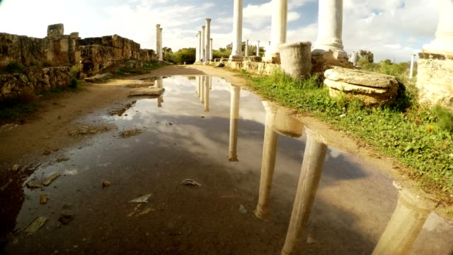 Vertical panorama Fresh Spring view Colonnade of Roman Agora reflections of columns blue sky and clouds in puddle antique town Salamis video