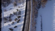 AERIAL, vertical: Single car driving along a road in winter, slow motion video
