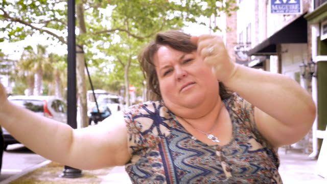 Very happy overweight woman urban dancing and jammin in the streets of a city video