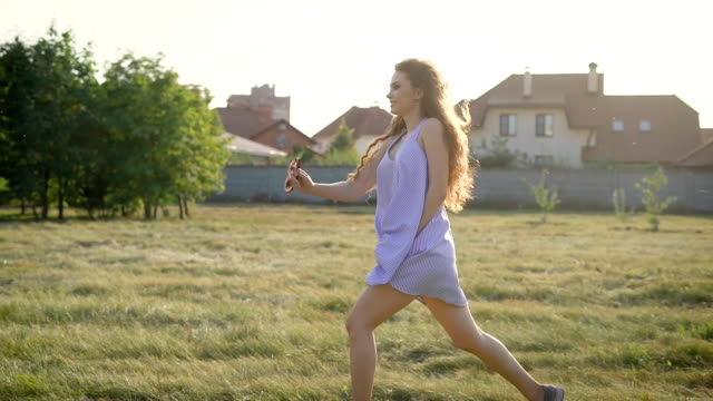 Very happy young beautiful woman running alone across the field wearing dress and enjoying her life video