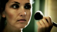 A very stylish toned footage of a woman applying her make-up before a big evening video