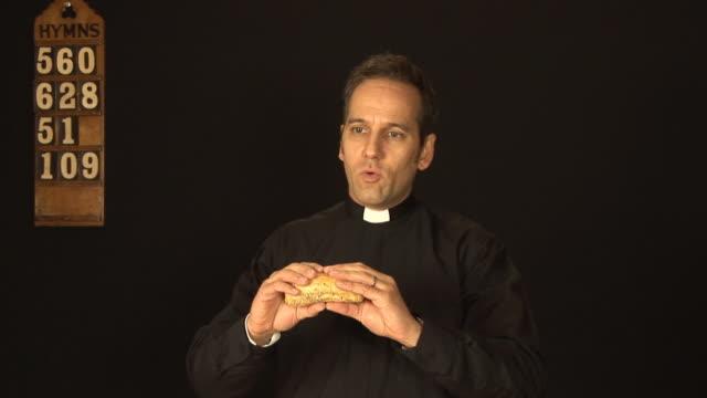 Vicar / Priest breaking bread in church service video
