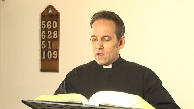 Vicar / Priest reading The Bible - HD & PAL video