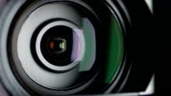 Video camera lens, showing zoom and glare, come to the shadow, close up video