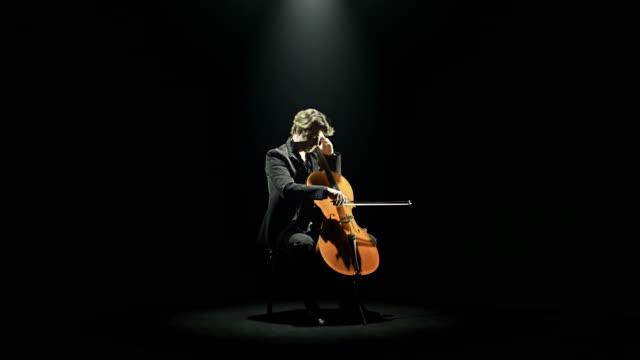 HD video cellist tunes his cello black background video
