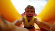 4K Video: Little boy slides fast by the inflatable slide into the water pool with active camera in front of his face video
