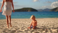 video of a boy palying in the sand on a tropical beach video