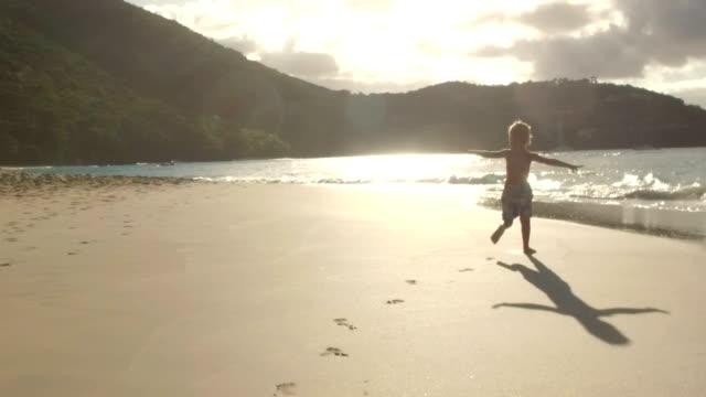 video of a boy running down a tropical beach video