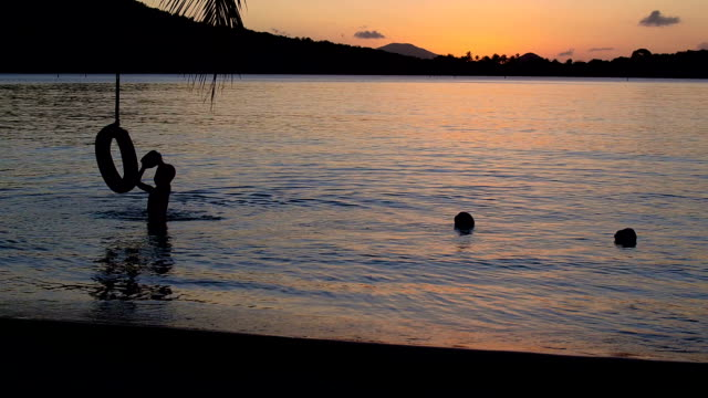video of a child playing tire swing on a tropical beach video