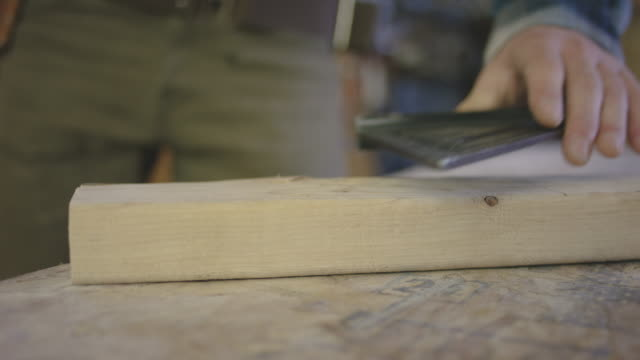 Video of a general construction contractor using a square to draw a mark on a 2x4 video