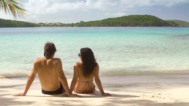 video of a honeymoon couple sunbathing at a Caribbean beach video