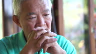 video of Asian senior guy with hand on face thinking, worry and sad video