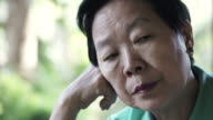 video of Asian senior woman with hand on face thinking, worry and sad video