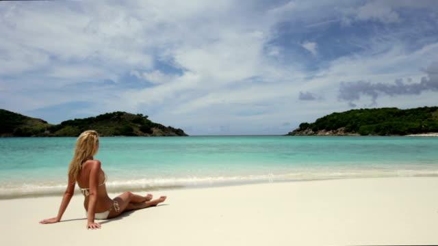 video of bikini woman sunbathing at a Caribbean beach video