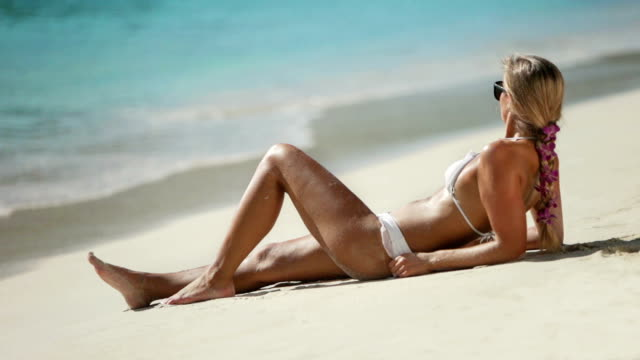 video of bikini woman sunbathing by the Caribbean beach shoreline video