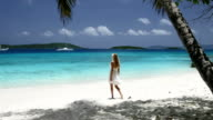 video of blonde-haired woman walking along the beach shoreline video