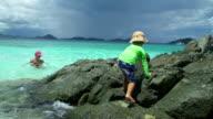 video of child climbing the rocks on a beach shoreline video