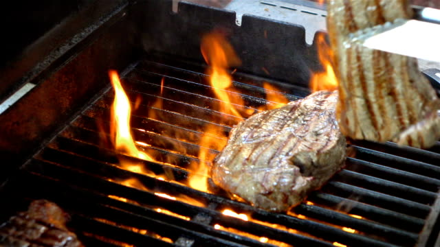 Video of cooking steaks on the fire-real slow motion video