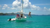 video of couple jumping off a sailboat in the Caribbean video