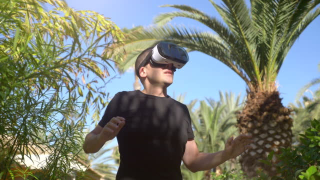 Video of man exploring virtual reality in tropical garden in 4k video