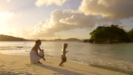 video of mother and child playing on a Caribbean beach video