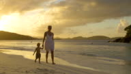 video of mother and child walking along the beach shoreline video