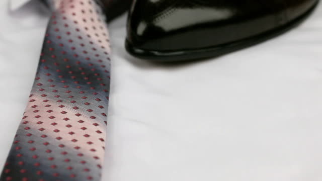 Video of red tie, men's shoes on a white shirt. Dolly shot. Close-up. video