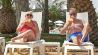 Video of senior couple drinking cocktails on sunbeds in 4K video